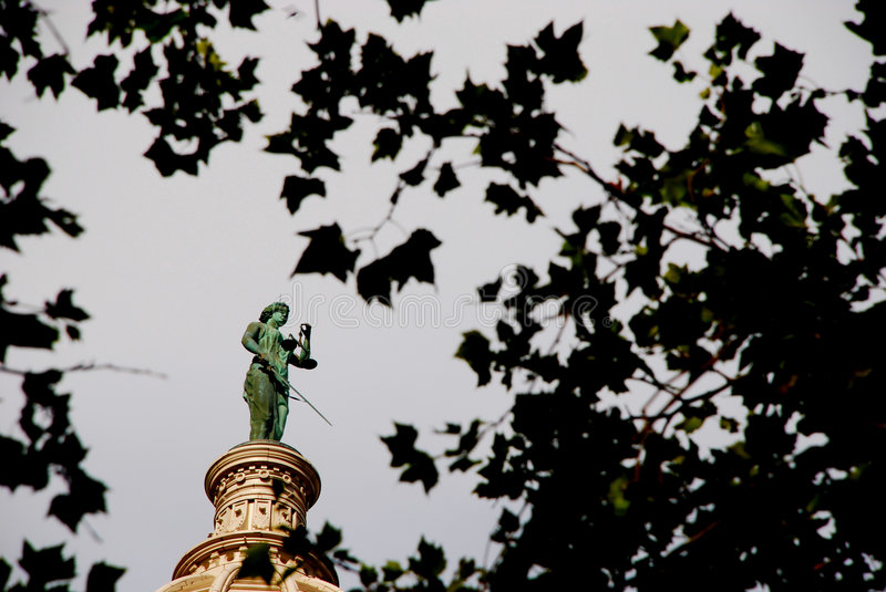 Lady Justice. This is a shot of the Lady Justice statue on top of a courthouse dome.Image captured peering through some tree leaves royalty free stock image