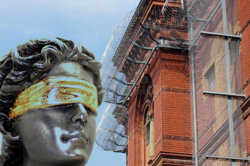 Lady Justice in front of barbed wire and prison walls royalty free stock photography