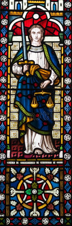 Lady Justice Stained Glass Window. Stained glass window showing Lady Justice holding a sword and a pair of weighing scales. Justice and fairness concept royalty free stock photography