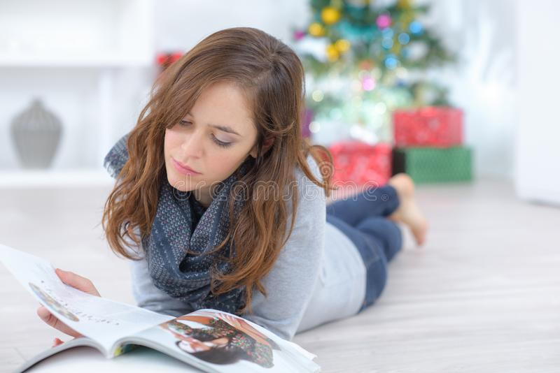 Lady layed on floor reading magazine royalty free stock images