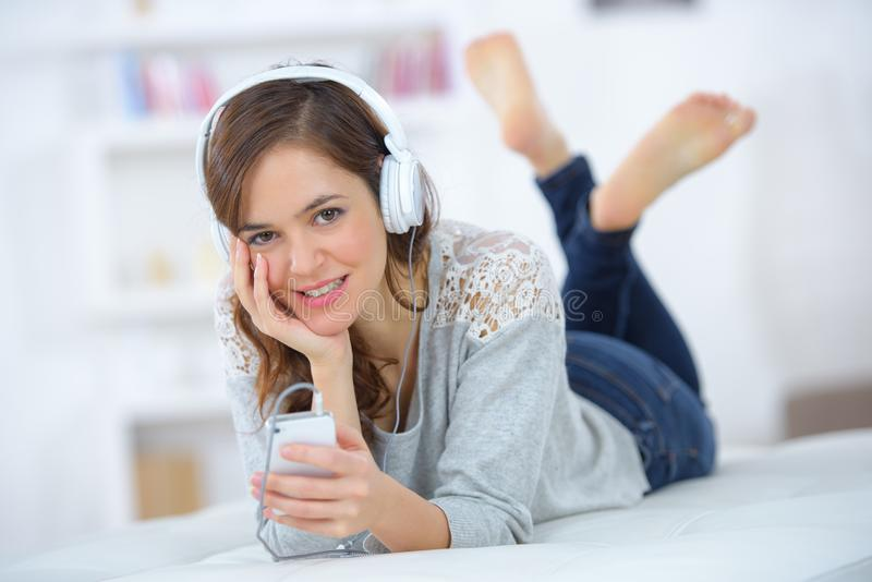 Lady layed on front listening to mp3 player royalty free stock image