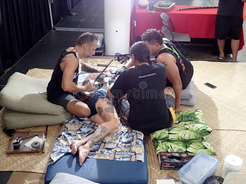 Lady lays on floor as she gets tattoo. Honolulu - August 6, 2017: Lady lays on floor as she gets tradition Hawaiian tattoo from two men at the Hawaii Tattoo Expo royalty free stock photos