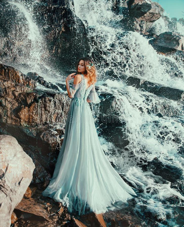 Lady in light long blue flying dress, water nymph stands near large waterfall. Sweet lady in light long blue flying dress, water nymph stands near large royalty free stock photography