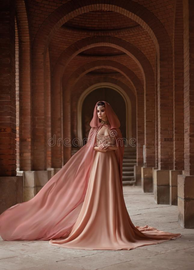 Lady in long pink dress in road coat with a hood is walking along old castle. A luxurious lady in a long pink dress in a road coat with a hood is walking along royalty free stock photos