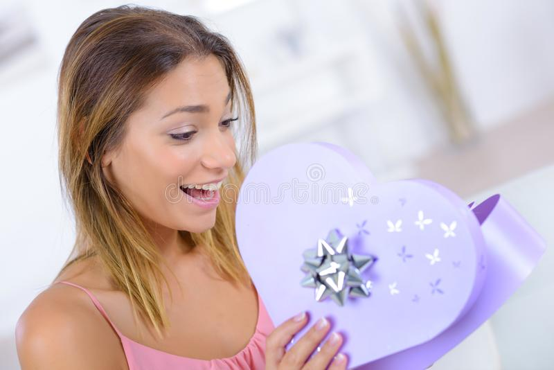 Lady looking excitedly into heart shaped giftbox royalty free stock images