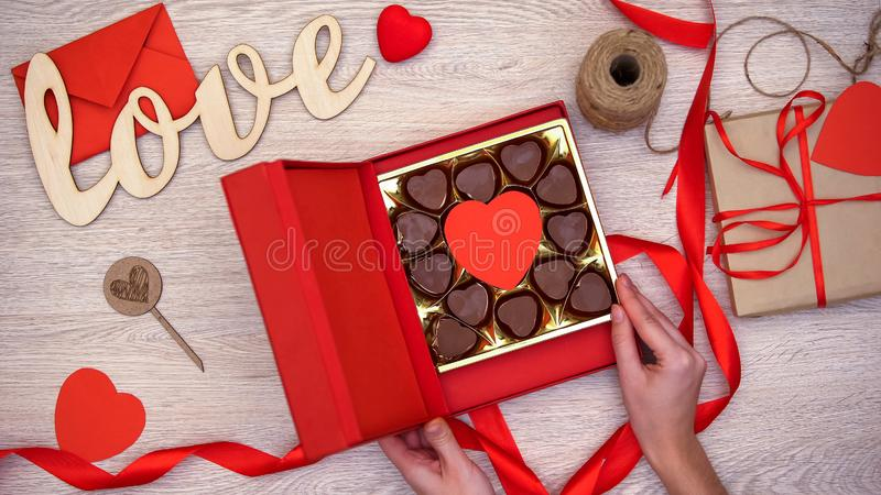 Lady opening Valentines giftbox with heart-shaped chocolate candies, aphrodisiac stock photos