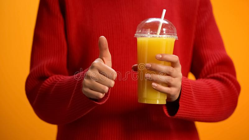 Lady with orange juice, hand showing thumbs up, healthy citrus cocktail, energy. Stock photo stock images