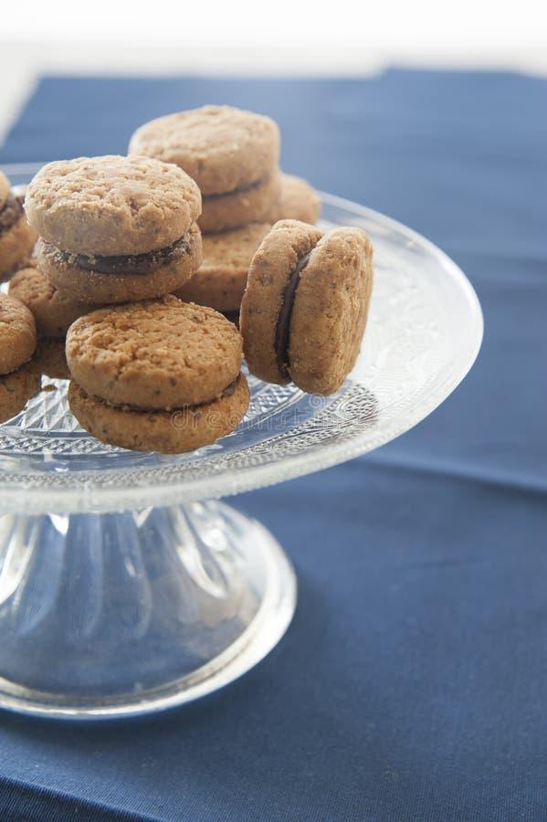 Lady& x27; os beijos de s no bolo de vidro estão trabalhados Toalha de mesa azul de Prússia como um fundo imagem de stock