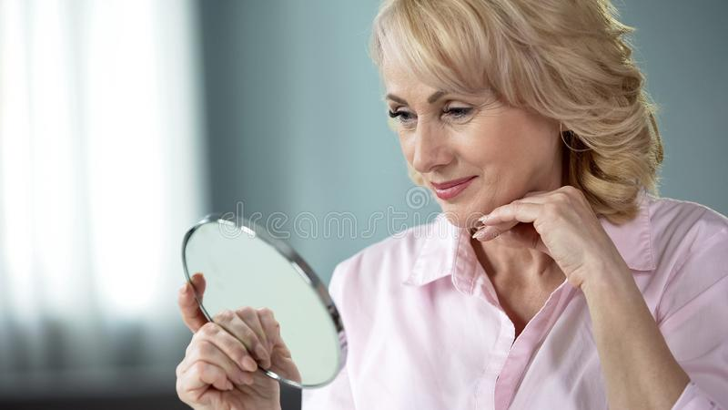 Lady over 50 looking at herself in mirror, rejoicing at result of skin lifting. Stock photo royalty free stock photography