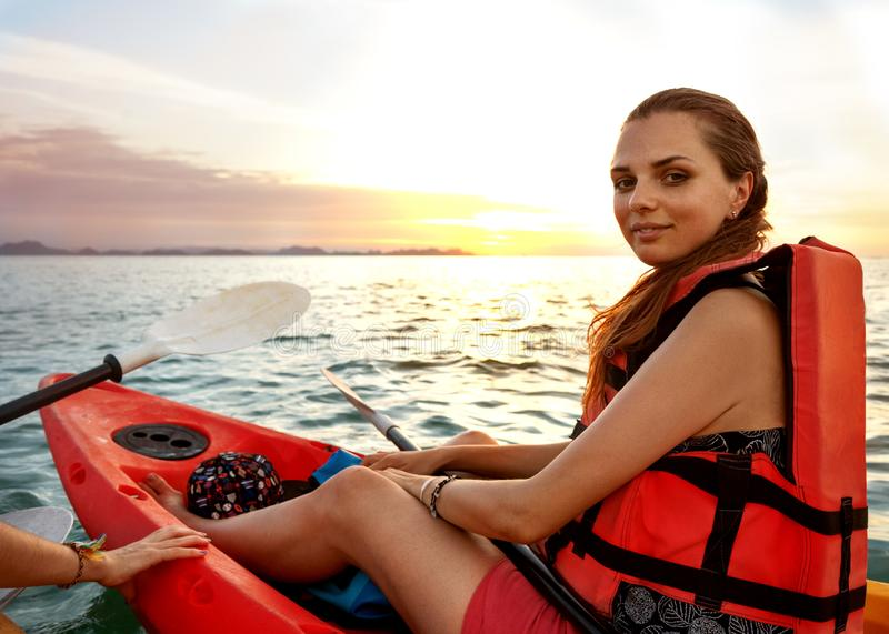 Lady paddling the kayak in the calm tropical bay at sunset royalty free stock images