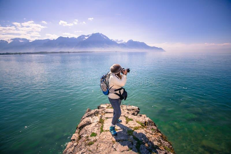 Lady Photographer with lake Geneva and mountain landscape at Chateau de Chillon - Veytaux, Switzerland stock image