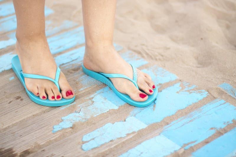 Lady& x27 ; pieds de s en sandales sur la plage images libres de droits
