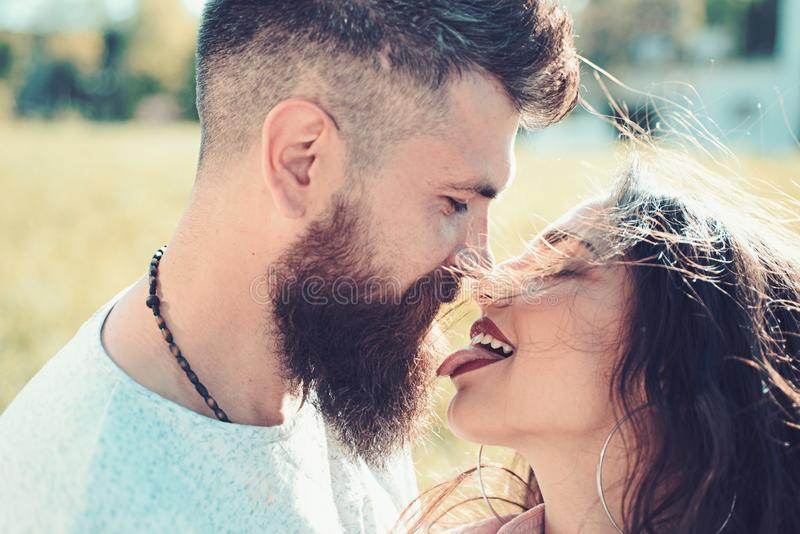 Lady with pink tongue licking bearded macho. Couple kissing outdoors, nature on background, close up. Kiss concept stock image