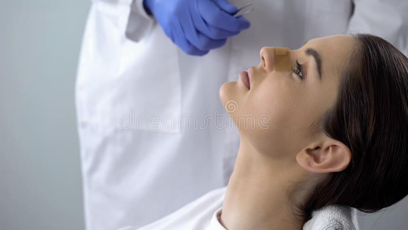 Lady with plaster on nose, doctor examining patients face after plastic surgery royalty free stock photography