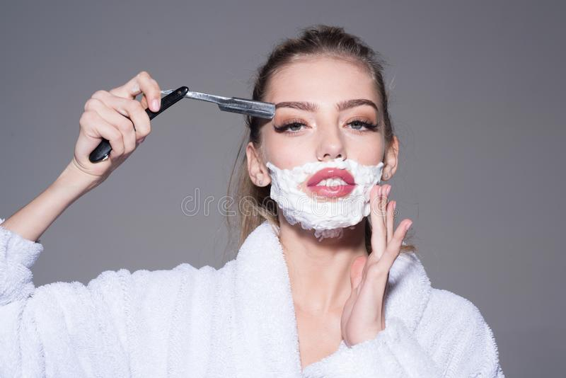Lady play with sharp blade of straight razor. Girl on dreamy face wears bathrobe, grey background. Woman with face royalty free stock photos