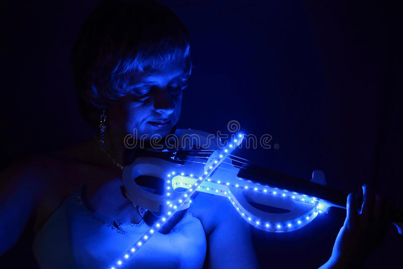lighting for plays. the lady plays on a glowing violin lighting for s