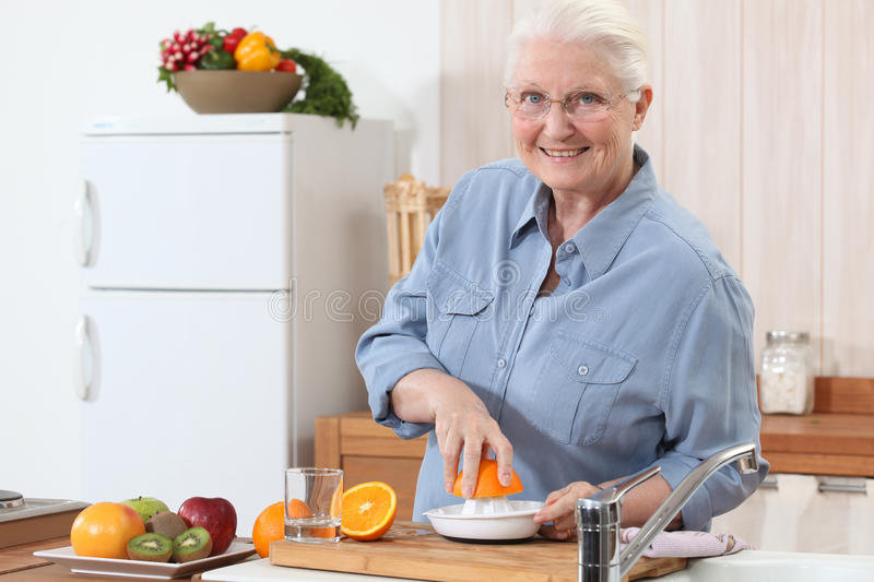 Lady pressing oranges. royalty free stock image