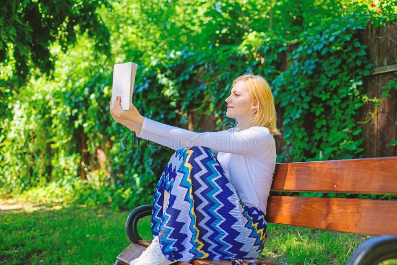 Lady pretty bookworm busy read book outdoors sunny day. Literary critic. Woman concentrated reading book in garden. Woman prepare review about bestseller. Girl stock photography