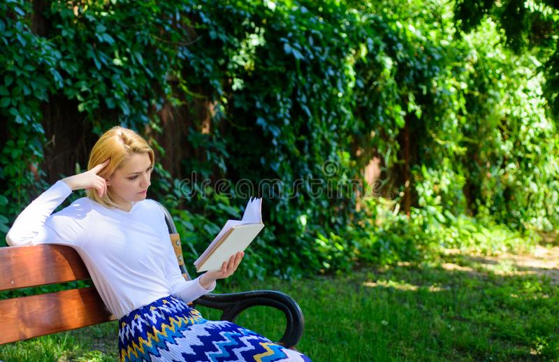 Lady pretty bookworm busy read book outdoors sunny day. Woman concentrated reading book in garden. Girl sit bench stock photo