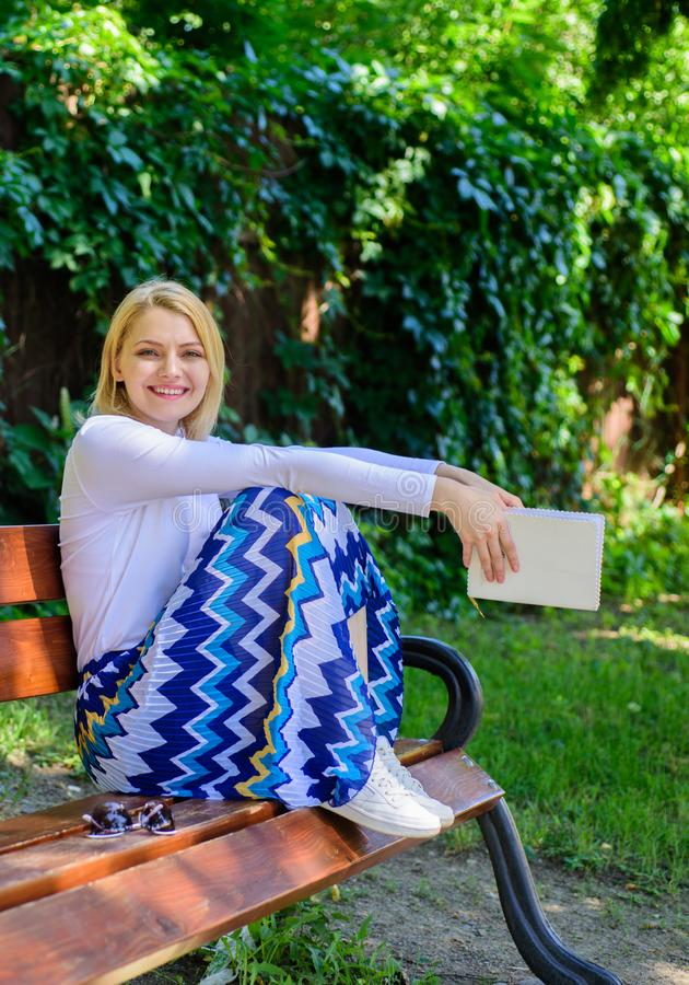 Lady pretty happy hold book garden sunny day. Girl sit bench relaxing with book, green nature background. Just finished royalty free stock image