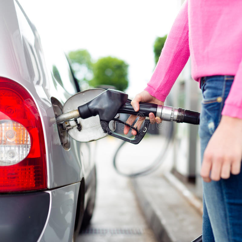 Lady pumping gasoline fuel in car at gas station. royalty free stock images