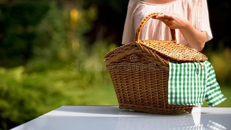 Lady putting picnic basket on table, preparing for family dinner outdoors royalty free stock images