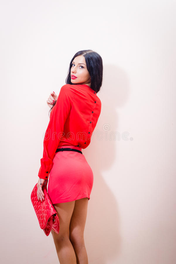 Lady in red: beautiful, tempting brunette woman in red dress with handbag standing looking at camera over shoulder royalty free stock photo