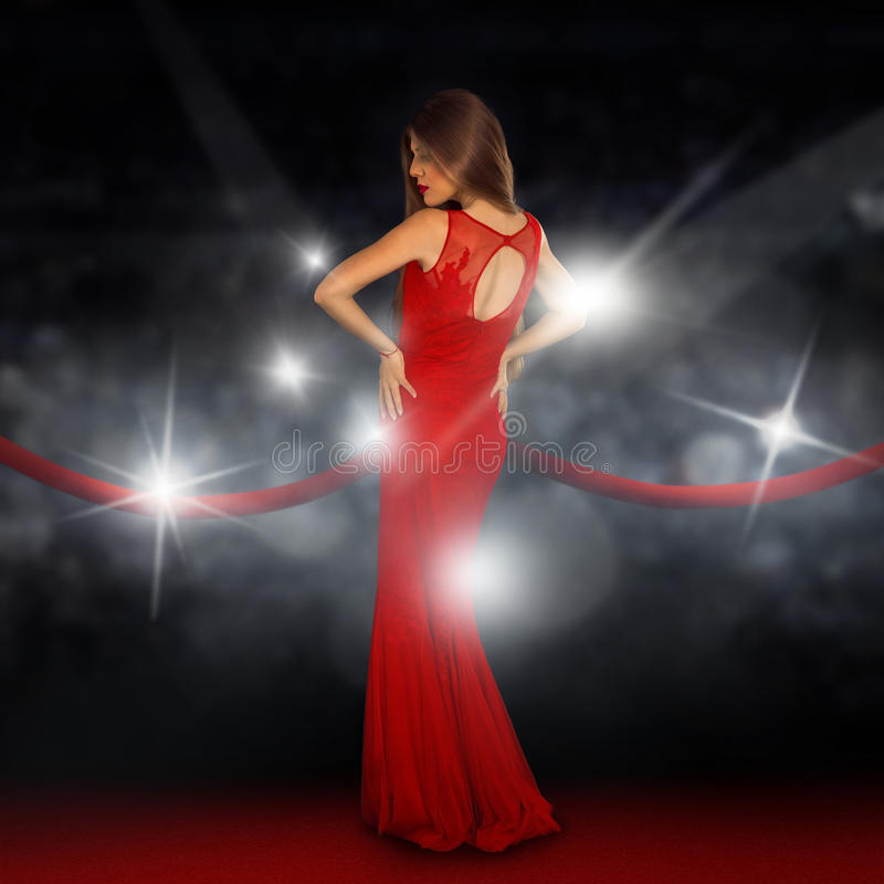 Lady on red carpet is posing in paparazzi flashes royalty free stock photography