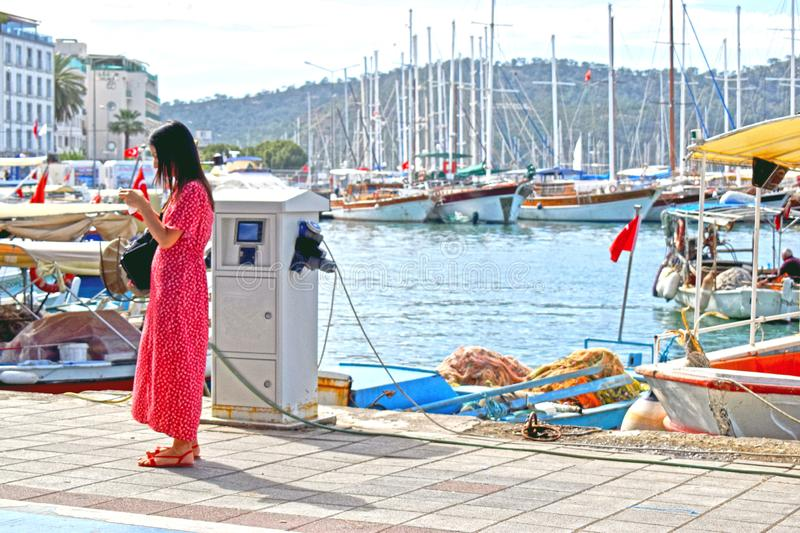 A lady in a red dress checking her phone by the Turkish Harbour royalty free stock photography