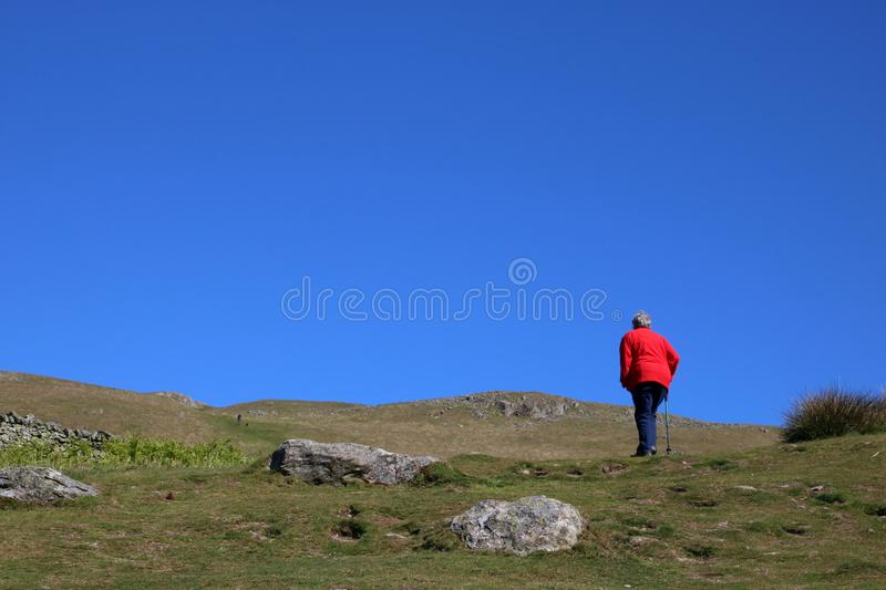 Lady in red jacket walking, hillside path, Cumbria stock photography