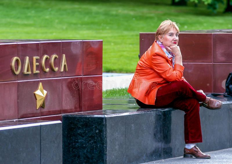 Lady in red sitting in the Alexander`s garden of Moscow Kremlin. Odessa city memorial in the Moscow park. royalty free stock images