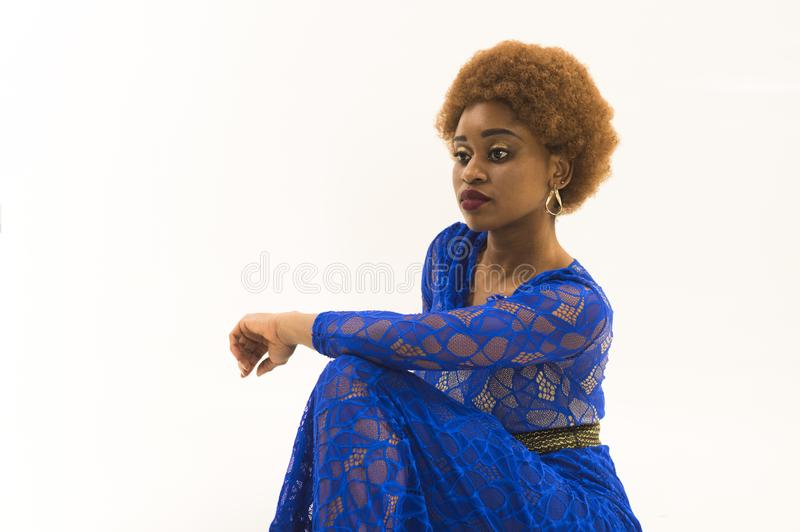 Lady on relaxed face with makeup and afro hairstyle. Lady in dress made out of lace. African females beauty concept stock images