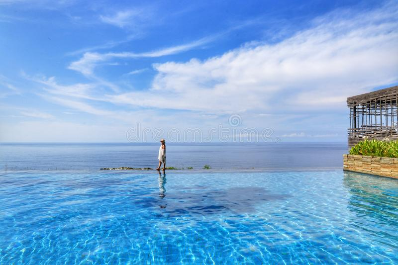 Lady relaxing and looking at beautiful landscape in luxury infinity pool. With blue sky on a sunny day. Views from Alila Villas Uluwatu Resort royalty free stock image
