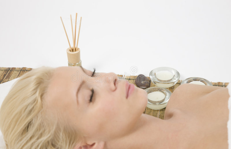 Lady relaxing on massage mat royalty free stock image