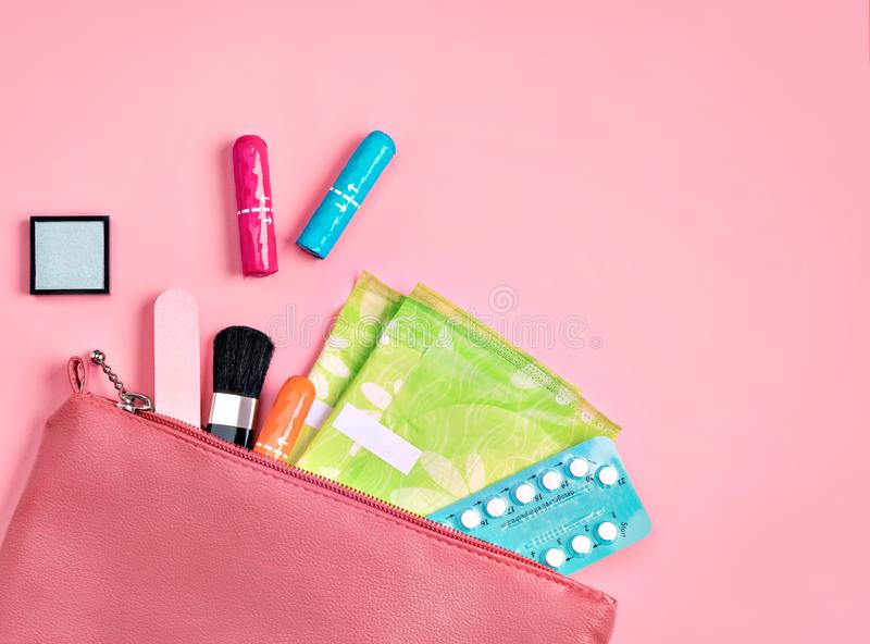 Lady`s bag. Sanitary pads and tampons in cosmetic bag on pink background. Concept of critical days, menstruation royalty free stock photography