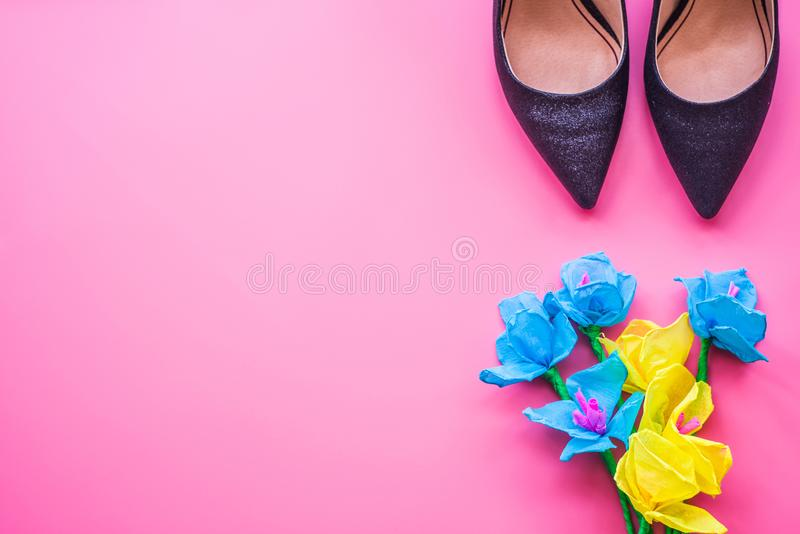 Lady`s high heels and paper flowers on pink background, top view. royalty free stock image