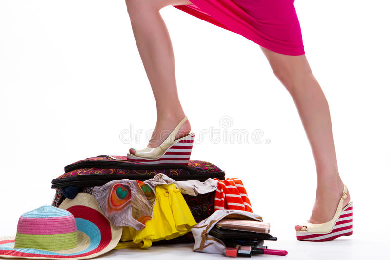 Lady's leg on filled suitcase. royalty free stock photos