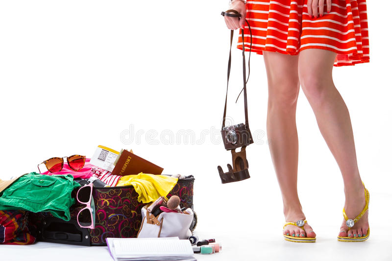 Lady's legs beside overfilled suitcase. Hand holds case with camera. This trip will be memorable. Last thing for baggage stock image