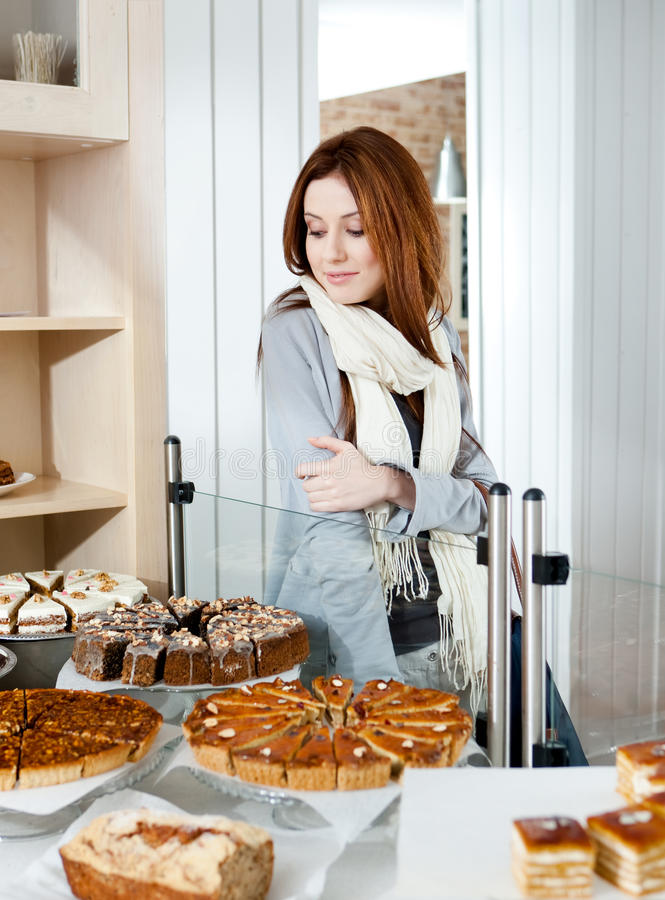 Download Lady In Scarf Looking At The Bakery Glass Case Royalty Free Stock Photography - Image: 26410847