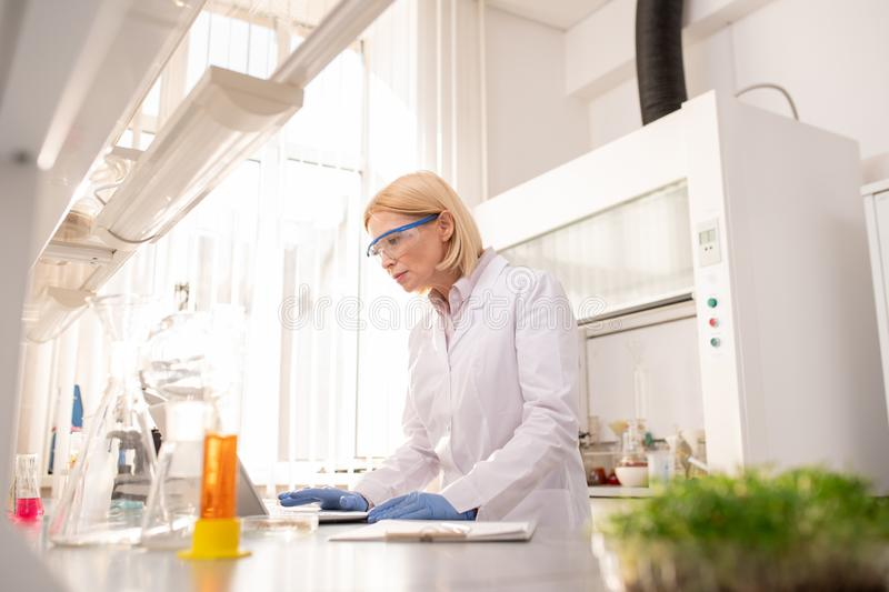Lady scientist viewing results of experiment royalty free stock photo