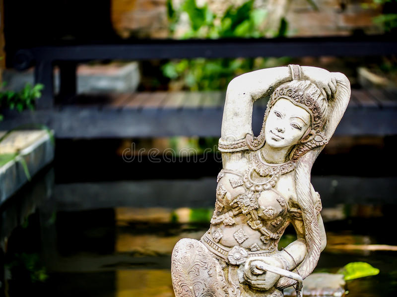 Lady sculpture in a Bali style garden stock photos