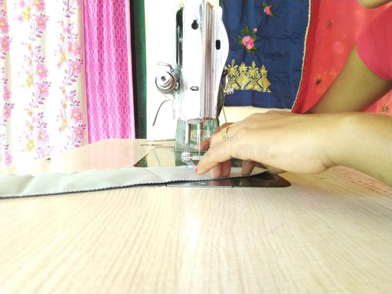 Lady sewing the clothes using machine stock photo