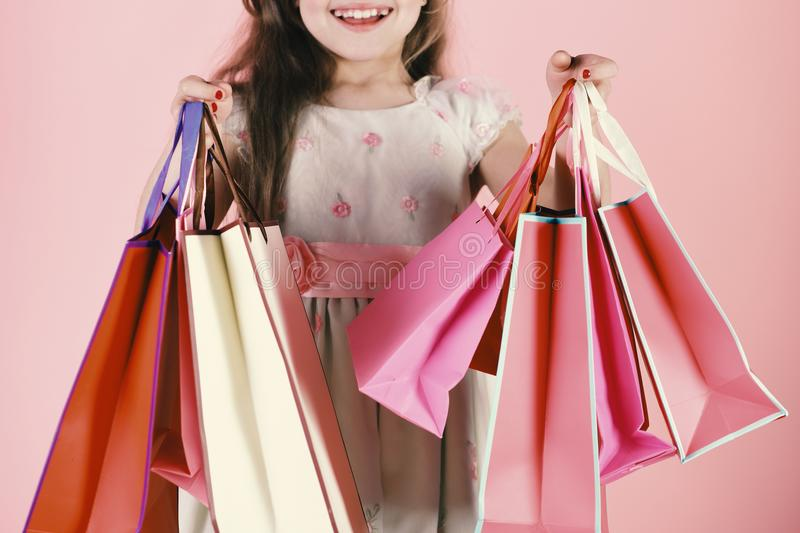 Lady shopper in dress, wavy hair. Girl holds shopping bags royalty free stock images