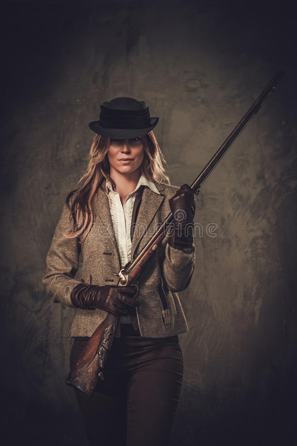 Lady with shotgun and hat from wild west on dark background. Lady with shotgun from wild west on dark background royalty free stock photos