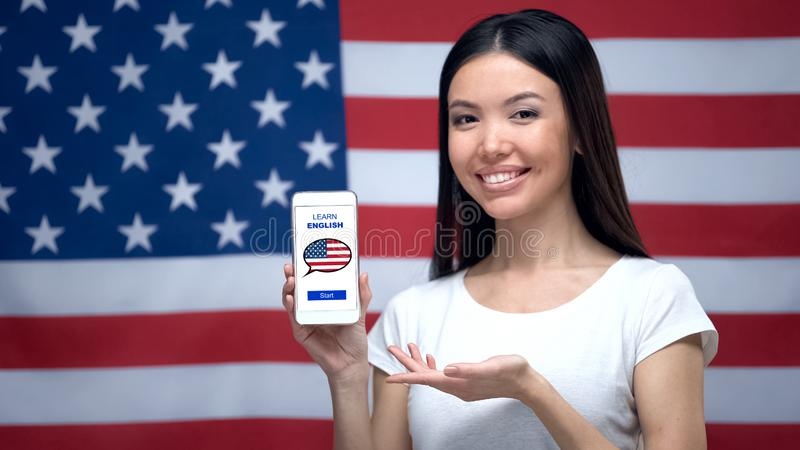 Lady showing cellphone with learn English app, USA flag on background, education. Stock photo stock photography