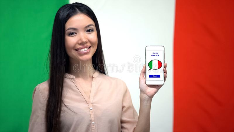 Lady showing cellphone with learn Italian app, flag on background, education. Stock photo stock images