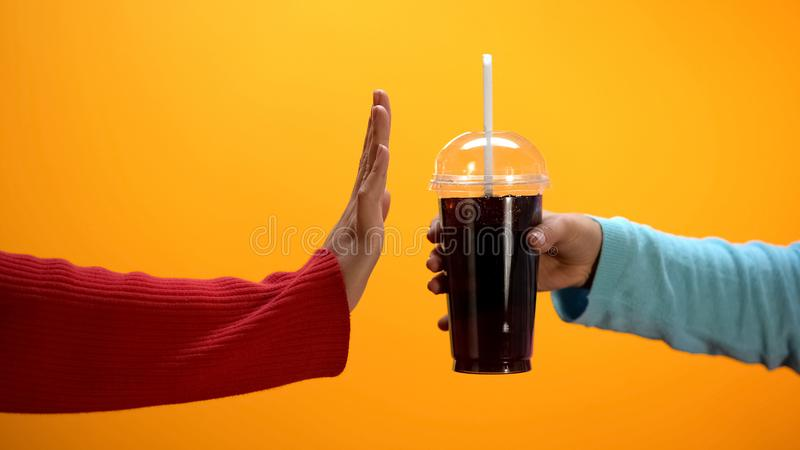 Lady showing stop gesture to soft drink on bright background, sugar overweight stock photography