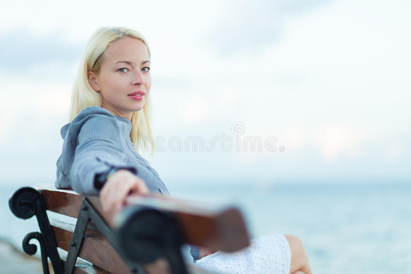 Lady sitting on a bench outdoors royalty free stock photography