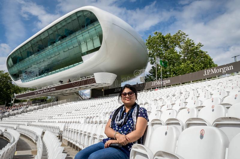 A lady sitting on the empty pavilion of Lord`s Cricket Ground with the media center in stock images
