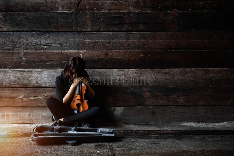 The lady is sitting on grunge surface cement floor,hold violin and bow in her arms,turn face down to volin,vintage and art style royalty free stock photography